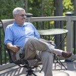 man smiling and sitting on outdoor deck