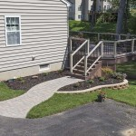 closer view of custom built patio deck with stairs, railings, and stone walkway