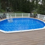 in ground pool surrounded by wolf decking and white vinyl railing