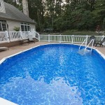 oval inground pool surrounded by faux wood deck