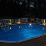 in ground pool with lights around pool fence