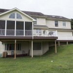 front view of enclosed porch deck and white vinyl railing