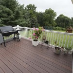 Custom vinyl deck with a grill and white vinyl railing